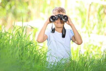 Little boy with binoculars outdoors. Summer camp