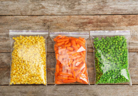Plastic bags with frozen vegetables on wooden background, top view