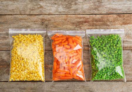Plastic zakken met bevroren groenten op houten achtergrond, bovenaanzicht