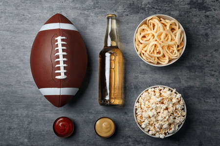 Table full of tasty snacks and beer prepared for watching American football on TV, top view Stock Photo