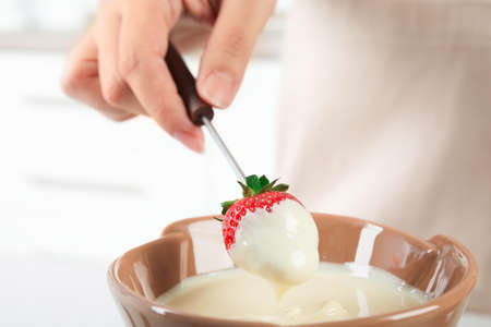 Woman dipping ripe strawberry into bowl with white chocolate fondue, closeup