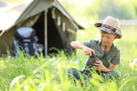Kleine jongen met kolf in de buurt van tent buitenshuis. Zomerkamp Stockfoto