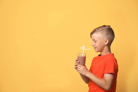 Little boy with glass of milk shake on color background 写真素材