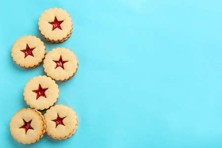Traditional Christmas Linzer cookies with sweet jam on color background, top view