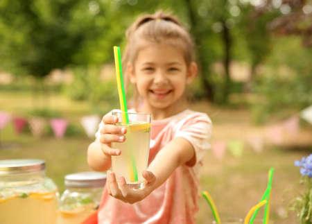 Little girl with natural lemonade in park