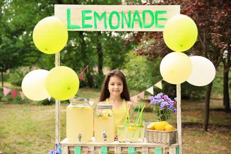 Niña en el puesto de limonada en el parque