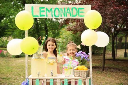 Kleine meisjes bij limonadetribune in park Stockfoto