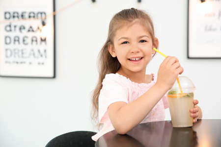 Little girl with natural lemonade at table indoors