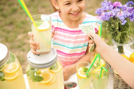 Niña vendiendo limonada natural en el stand en el parque
