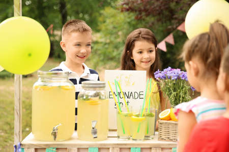 Little kids selling natural lemonade at stand in park