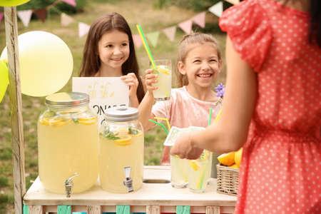 Kleine meisjes verkopen natuurlijke limonade aan vrouw bij stand in park