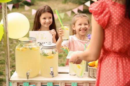 Little girls selling natural lemonade to woman at stand in park