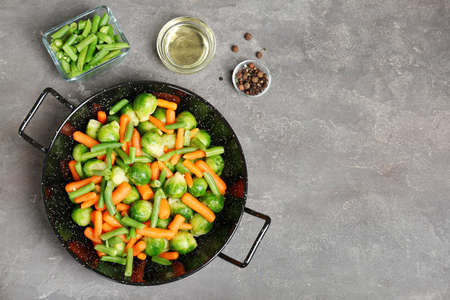 Composition à plat avec des légumes surgelés sur fond gris