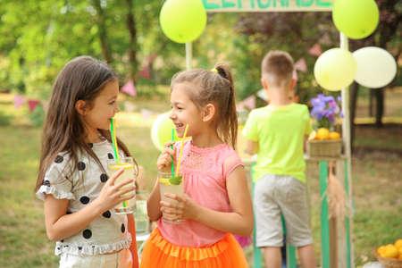 Little girls with natural lemonade in park