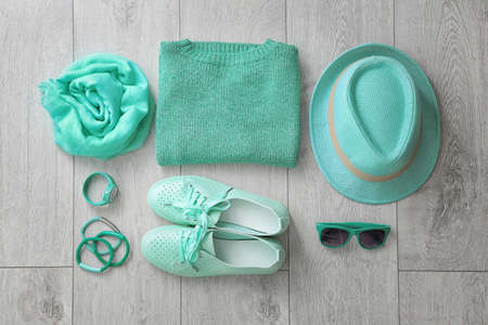 Flat lay composition with set of mint clothes and accessories on wooden background