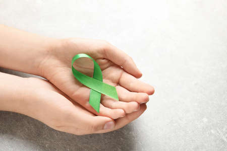 Woman holding green ribbon on grey background. Cancer awareness