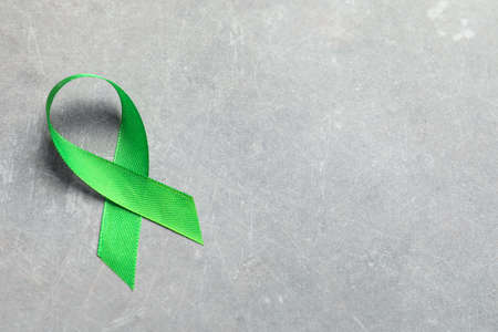 Green ribbon on grey background. Cancer awareness