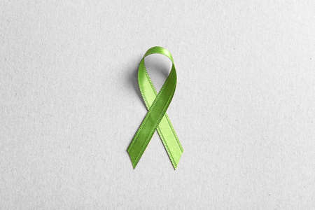 Green ribbon on color background, top view. Cancer awareness