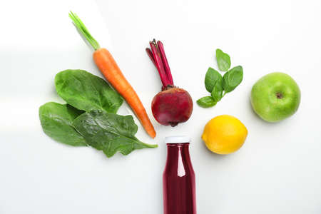 Glass bottle of fresh juice and ingredients on white background, top view
