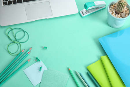 Workplace with stationery in mint color shades and laptop Stock Photo