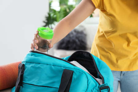 Young woman packing sports bag at home