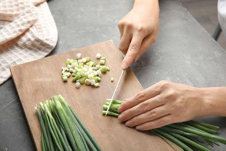 Woman cutting fresh green onion on wooden board Foto de archivo