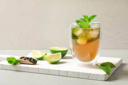 Glass with aromatic mint tea, fresh leaves and lime on wooden board