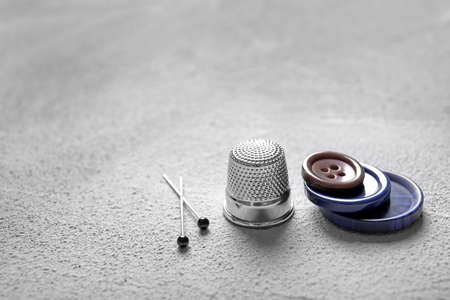 Set of tailoring accessories on grey background, closeup