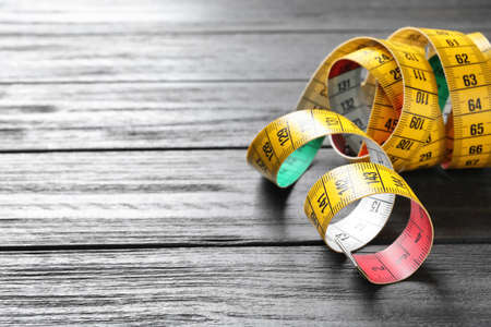 Measuring tape on wooden background. Tailoring equipment