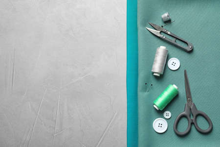 Set of tailoring accessories and fabric on grey background, top view