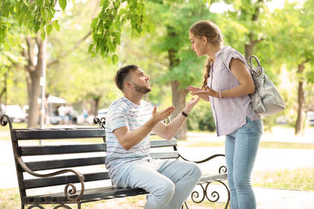 Young couple arguing while sitting on bench in park. Problems in relationship