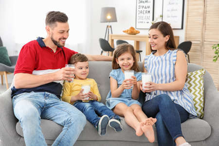 Happy family with glasses of milk in living room
