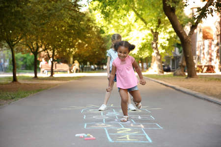 Little children playing hopscotch drawn with colorful chalk on asphalt Stockfoto