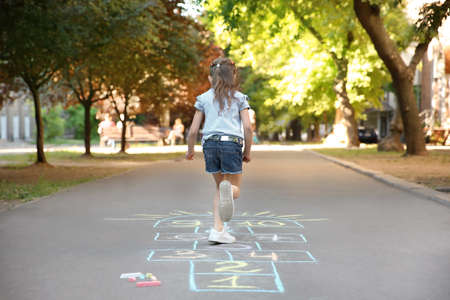 Little child playing hopscotch drawn with colorful chalk on asphalt Stockfoto