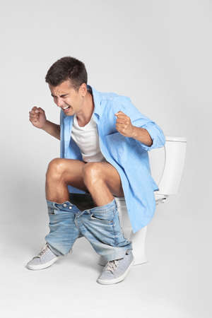 Young man suffering from diarrhea on toilet bowl against gray background Archivio Fotografico