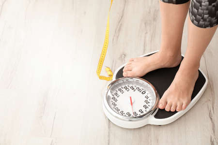 Woman with tape measuring her weight using scales on floor. Healthy diet