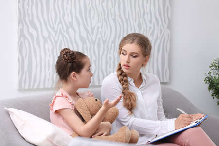 Young female psychologist working with little child in office