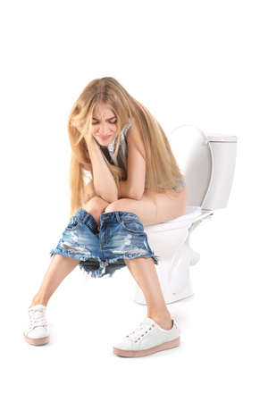 Young woman suffering from diarrhea on toilet bowl. Isolated on white