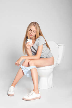 Young woman using mobile phone while sitting on toilet bowl against gray background