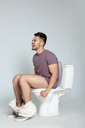 Young man suffering from diarrhea on toilet bowl against gray background Stock Photo