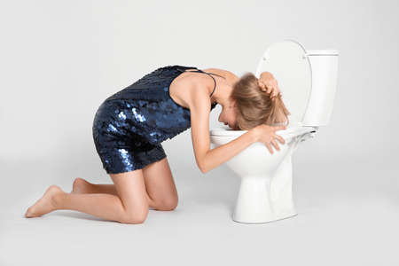Young woman vomiting in toilet bowl on gray background Stock Photo