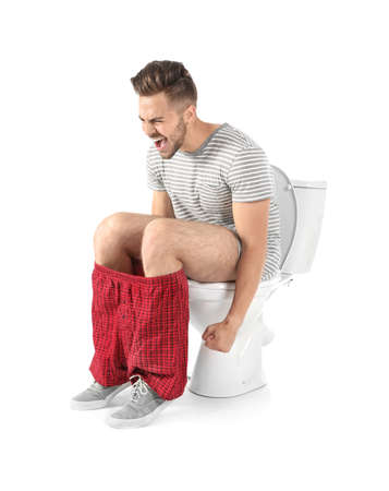 Young man suffering from diarrhea on toilet bowl. Isolated on white