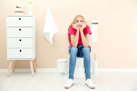 Young woman sitting on toilet bowl at home