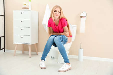 Jonge vrouw die lijdt aan diarree op de wc-pot thuis Stockfoto