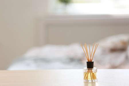 Aromatische riet luchtverfrisser op tafel tegen onscherpe achtergrond Stockfoto