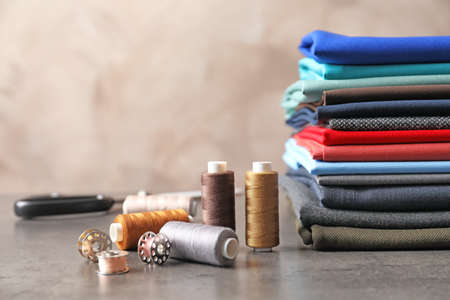 Bobbins with threads and stack of colorful fabrics on table. Tailoring accessories Stock Photo