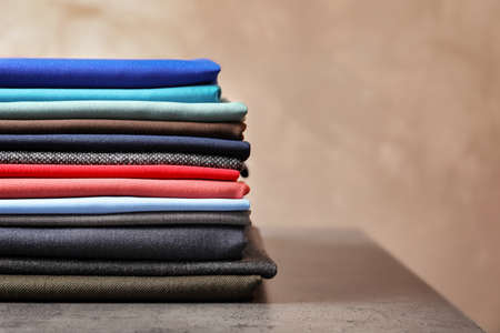 Stack of colorful fabrics for tailoring on table
