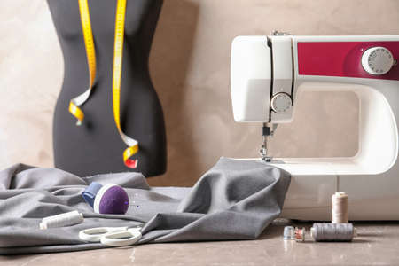 Sewing machine, fabric and accessories for tailoring on table Archivio Fotografico