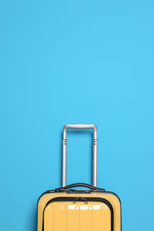 Packed bright yellow suitcase on color background Stock Photo
