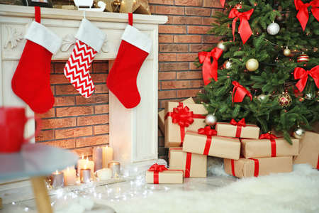 Beautiful Christmas tree and gifts near decorative fireplace with stockings indoors